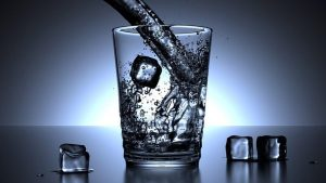 A glass of clear water with ice cubes to match.