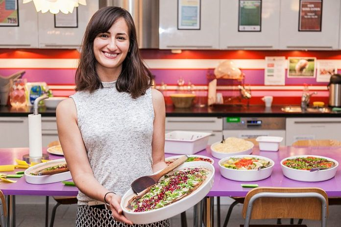 A smiling woman in a kitchen, pleased with the cooking hack that she has used.