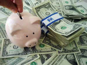 You can keep your costs down when you purchase food if you follow these simple tips. The image is of a piggy bank and a lot of dollar bills.