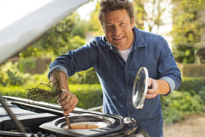 A picture of the famous chef himself, grilling on a car engine!