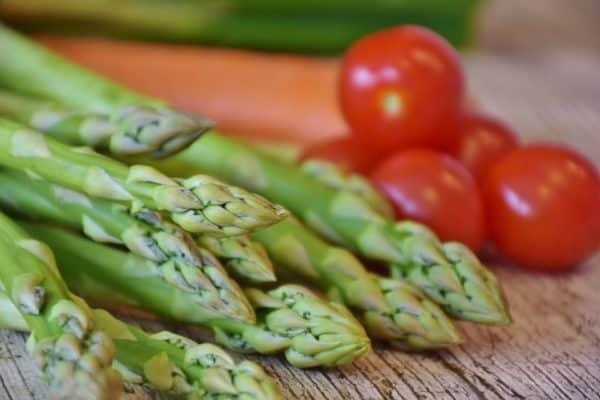 An image of tomatoes and asparagus, two plants that do well when planted together.