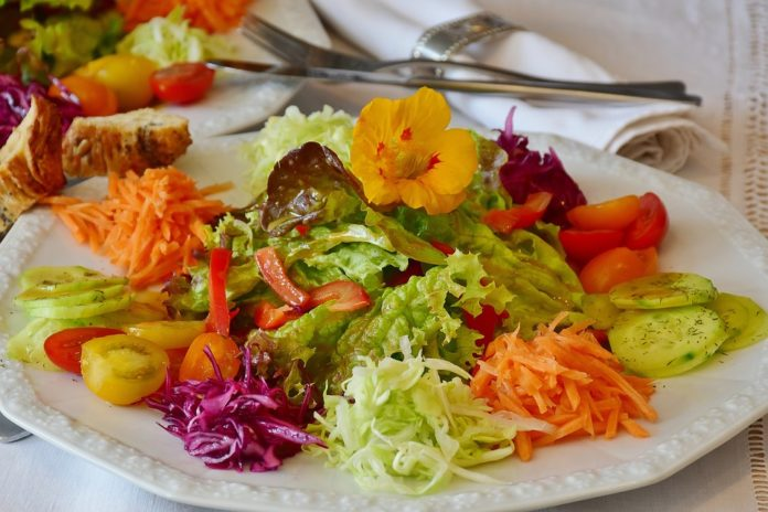 A delicious looking salad on a plate. You can make your own salads and save a lot of money.