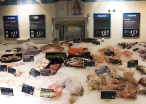 A typical arrangement of fish in a market or supermarket along with discounts marked up on the wall. Smart shopping saves money.