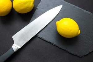 a kitchen knife with lemons on a cutting board