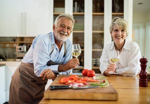 old couple drinking wine in the kitchen