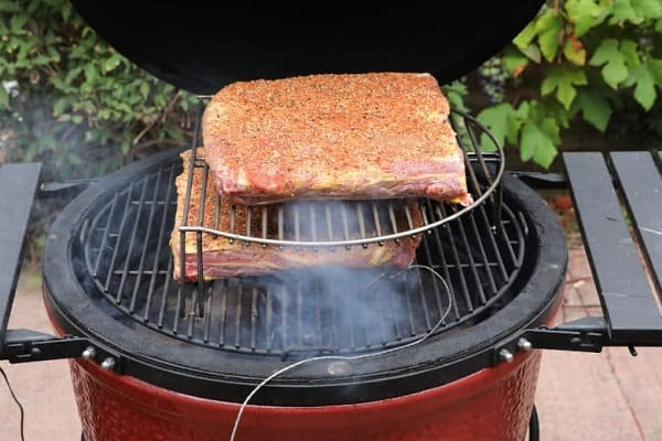 2 slabs of meat being grilled on a red grill